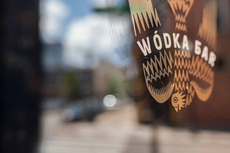 The Wodka Bar OTR sign on the door reflects the city of Cincinnati in the background
