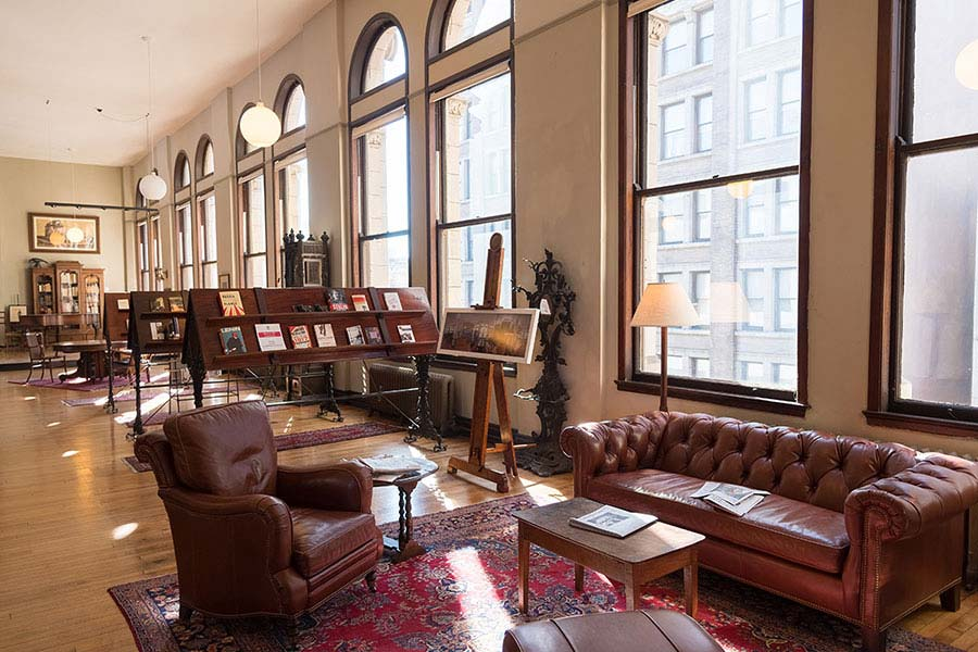 A sitting area with bright windows in the Mercantile Library