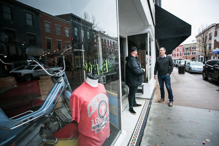 Designer Jason Snell and The Distiller Podcast host Brandon Dawson talk on the sidewalk outside BLDG in Covington Kentucky